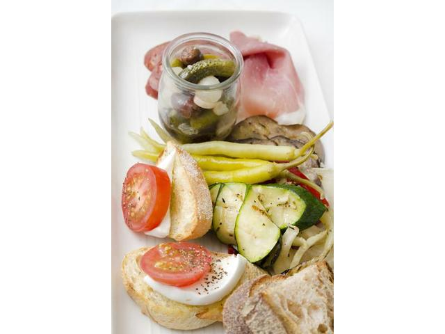 Antipasto platter with cured meats, pickled and grilled vegetables,